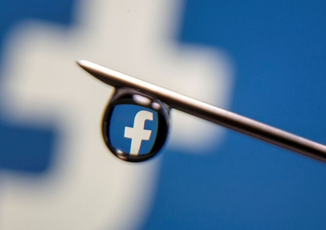 Facebook logo is reflected in a drop on a syringe needle in this illustration photo taken 16 March 2021