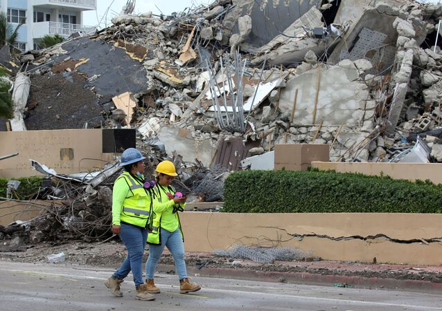 Rescue workers walk past debris after the managed demolition of the remaining part of Champlain Towers South complex as search-and-rescue efforts continue in Surfside, Florida, 6 July 2021.