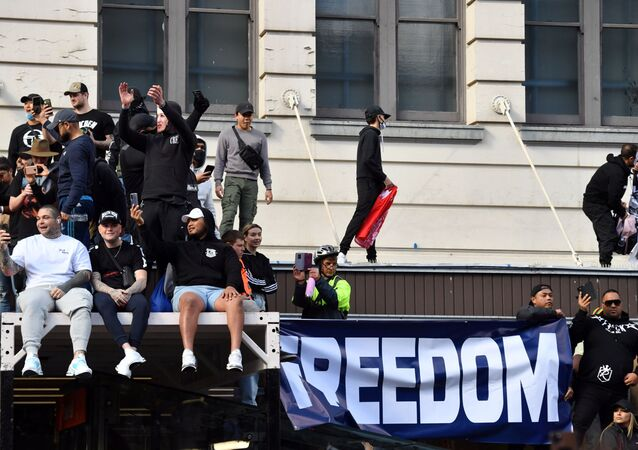 Protesters climb an awning outside Sydney Town Hall during an anti-lockdown rally, as an outbreak of the coronavirus disease (COVID-19) affects Sydney, Australia, 24 July 2021. AAP Image/Mick Tsikas via REUTERS.