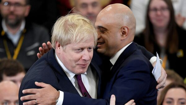 Britain's Prime Minister Boris Johnson is embraced by Britain's Chancellor of the Exchequer Sajid Javid before speaking to the workers as he visits a JCB factory during his general election campaign in Uttoxeter, Britain, December 10, 2019 - Sputnik International