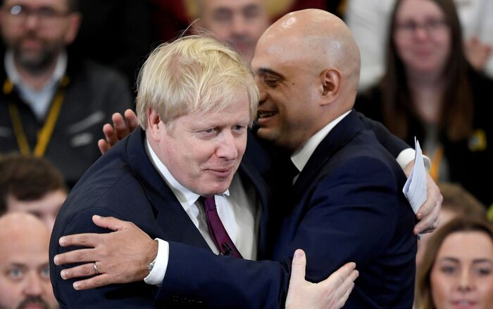Britain's Prime Minister Boris Johnson is embraced by Britain's Chancellor of the Exchequer Sajid Javid before speaking to the workers as he visits a JCB factory during his general election campaign in Uttoxeter, Britain, December 10, 2019
