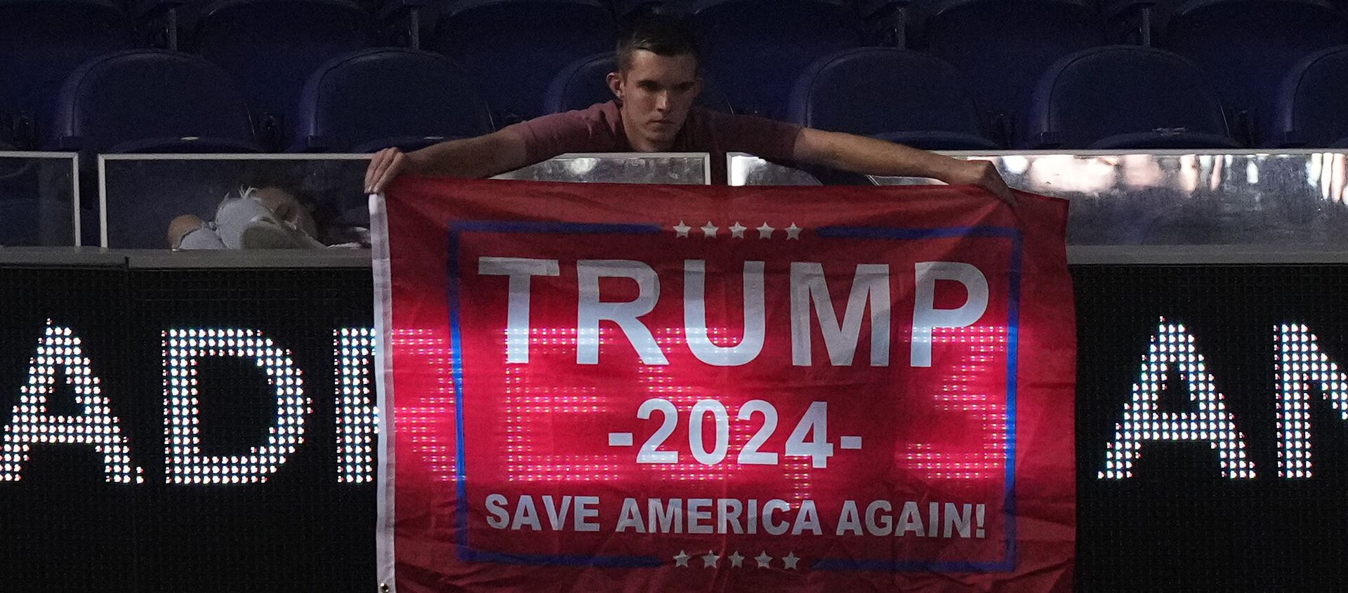 A fan displays a flag in support of former president Donald Trump in the upper deck after the game between the Miami Marlins and the San Diego Padres at loanDepot park - Sputnik International, 1920, 25.07.2021