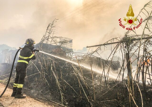 A firefighter battles the flames after a large wildfire broke out near Santu Lussurgiu, Sardinia, Italy July 24, 2021.