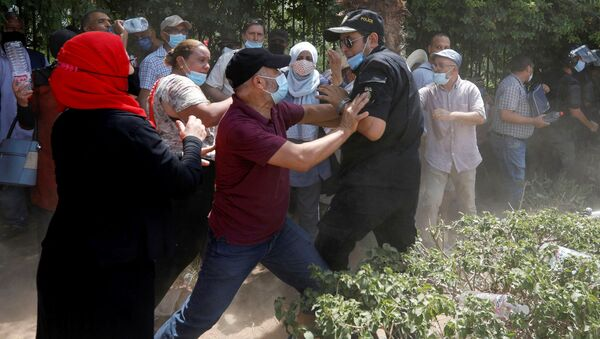 A supporter of Tunisia's biggest political party, the moderate Islamist Ennahda, scuffles with a police officer near the parliament building in Tunis, Tunisia July 26, 2021. - Sputnik International