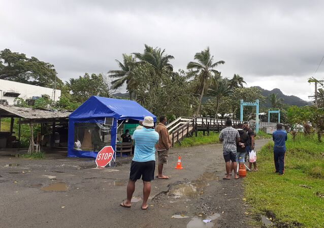 Family members wait at the entrance to a village settlement to deliver food to relatives that are in lockdown as an outbreak of the coronavirus disease (COVID-19) affects Lami, Fiji, June 26, 2021.