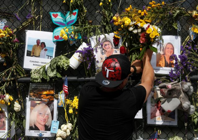 A man places flowers on a makeshift memorial for the victims of the Surfside's Champlain Towers South condominium collapse in Miami, Florida, U.S., July 8, 2021