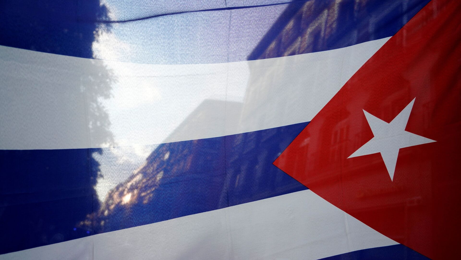 The silhouette of the city is seen through a Cuban flag during a protest against the  U.S. economic embargo in Cuba - Sputnik International, 1920, 27.07.2021
