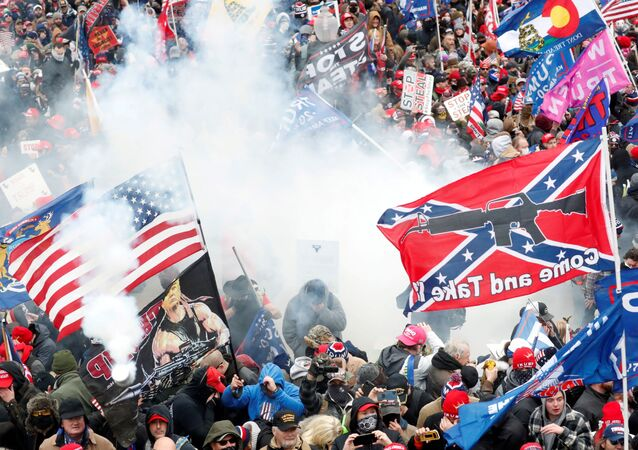 Tear gas is released into a crowd of protesters, with one wielding a Confederate battle flag that reads Come and Take It, during clashes with Capitol police