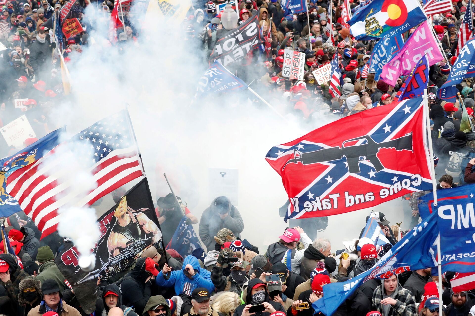 Tear gas is released into a crowd of protesters, with one wielding a Confederate battle flag that reads Come and Take It, during clashes with Capitol police - Sputnik International, 1920, 07.09.2021