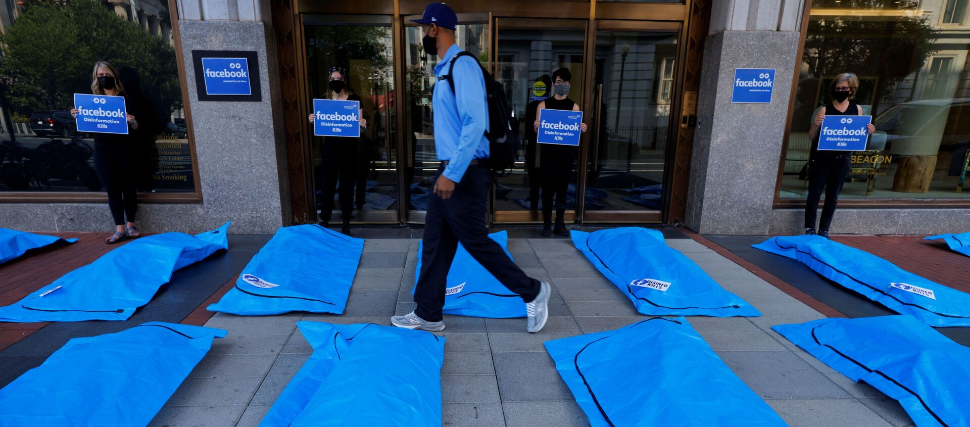 A pedestrian walks through an art installation of body bags as demonstrators protest against Facebook and what they claim is disinformation regarding coronavirus disease (COVID-19) on the social media giant's platform, outside Facebook headquarters in Washington, U.S., July 28, 2021 - Sputnik International, 1920, 29.07.2021