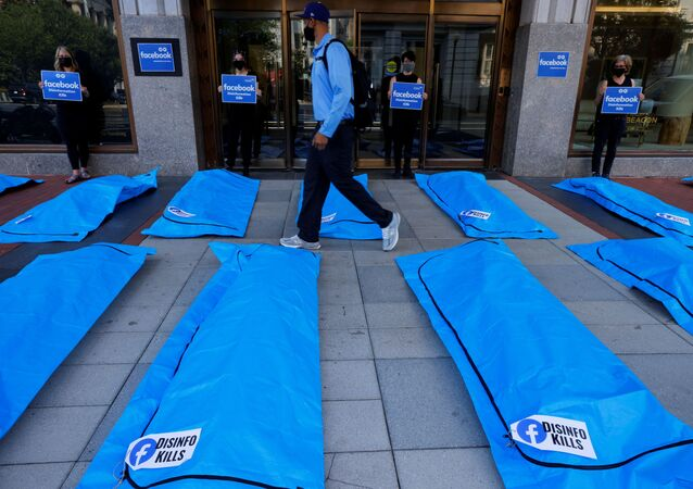 A pedestrian walks through an art installation of body bags as demonstrators protest against Facebook and what they claim is disinformation regarding coronavirus disease (COVID-19) on the social media giant's platform, outside Facebook headquarters in Washington, U.S., July 28, 2021