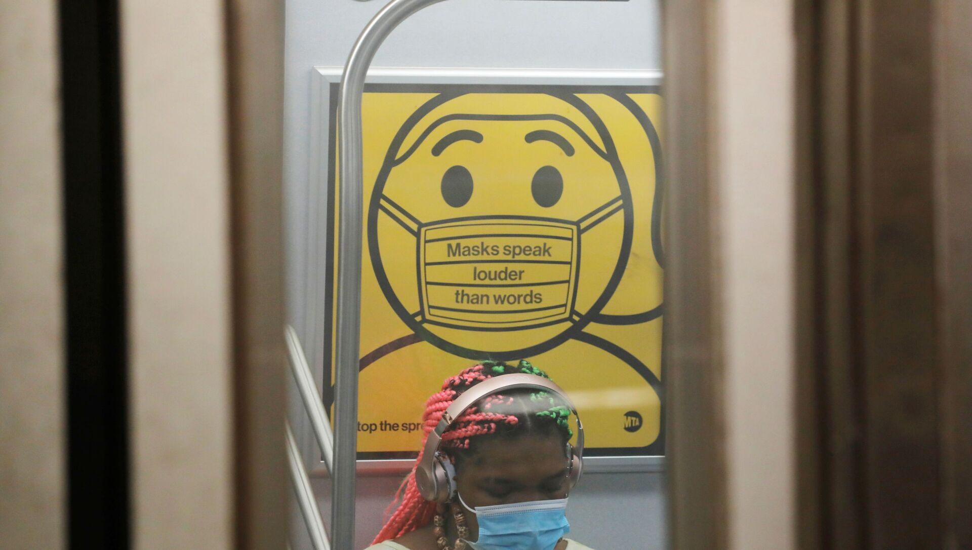 A commuter wears a mask under public safety signage as cases of the infectious coronavirus Delta variant continue to rise in New York City, New York, U.S., July 26, 2021. REUTERS/Andrew Kelly - Sputnik International, 1920, 29.07.2021