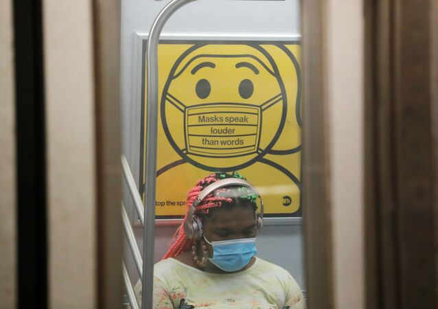 A commuter wears a mask under public safety signage as cases of the infectious coronavirus Delta variant continue to rise in New York City, New York, U.S., July 26, 2021. REUTERS/Andrew Kelly