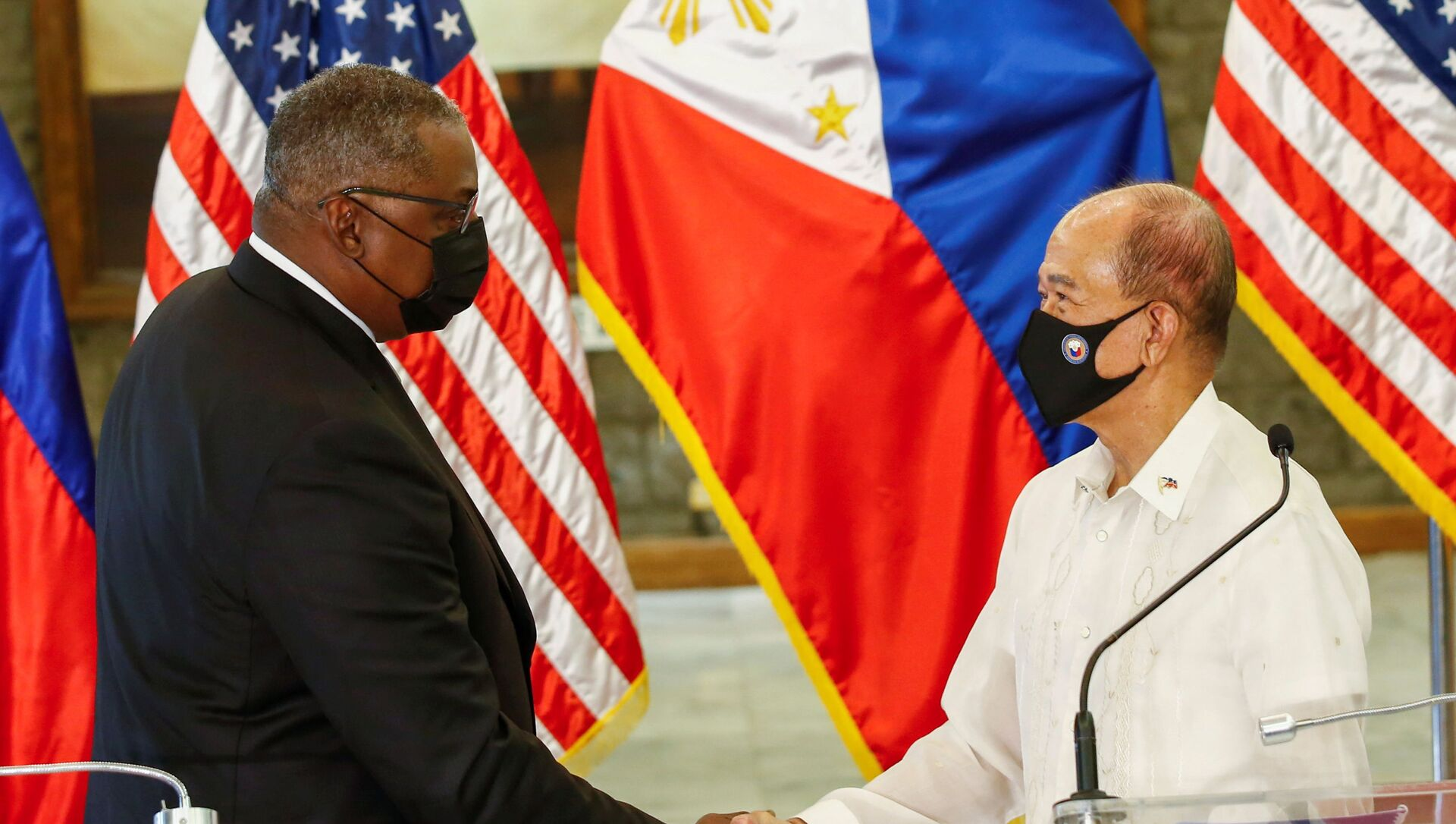 United States Defense Secretary Lloyd Austin (L) and Philippines' Defense Secretary Delfin Lorenzana (R) shake hands after a bilateral meeting at Camp Aguinaldo military camp in Quezon City, Metro Manila, Philippines, July 30, 2021.  - Sputnik International, 1920, 30.07.2021