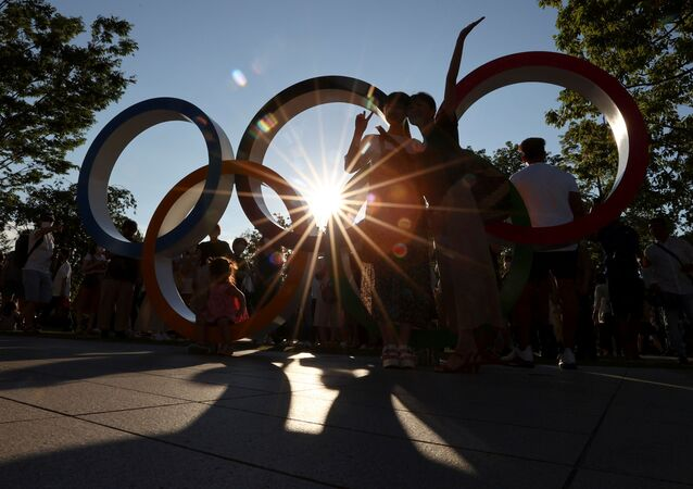 People pose for a photograph in front of an Olympic rings monument outside the National Stadium, the main stadium of Tokyo 2020 Olympic and Paralympic Games, amid the coronavirus disease (COVID-19) pandemic, in Tokyo, Japan July 31, 2021.  REUTERS/Issei Kato