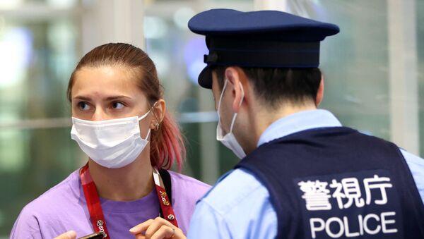 Belarusian sprinter Kristina Timanovskaya talks with police officers at Haneda International Airport in Tokyo, Japan. - Sputnik International