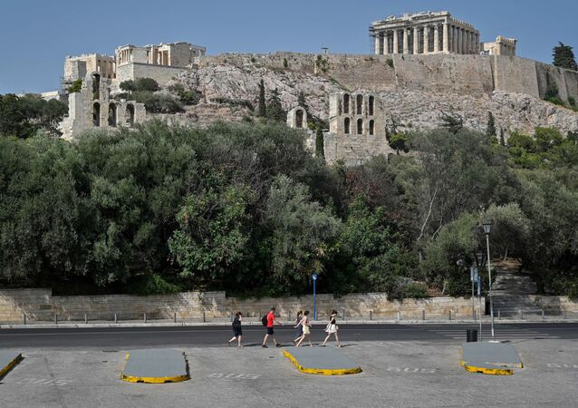 Tourists walk past empty Acropolis parking, as the archaeological site has closed  due to the heatwave in Athens on August 2, 2021.