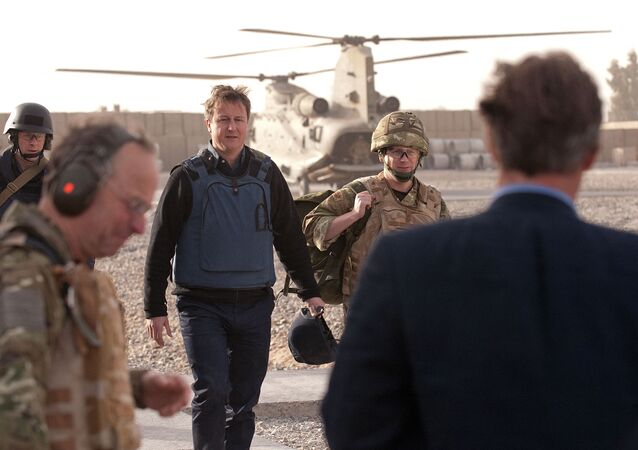 British Prime Minister David Cameron (C) arrives at Lashkar Gah base in Afghanistan on December 6, 2010. Cameron has made an unannounced trip to Afghanistan to demonstrate the growing stability in the country and to see how troops are helping to train up the Afghan security services.