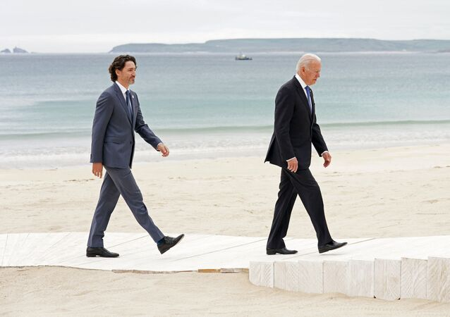 Canada's Prime Minister Justin Trudeau (L) and US President Joe Biden arrive to pose for the family photo during the G7 summit in Carbis Bay, Cornwall, south-west England on 11 June 2021.
