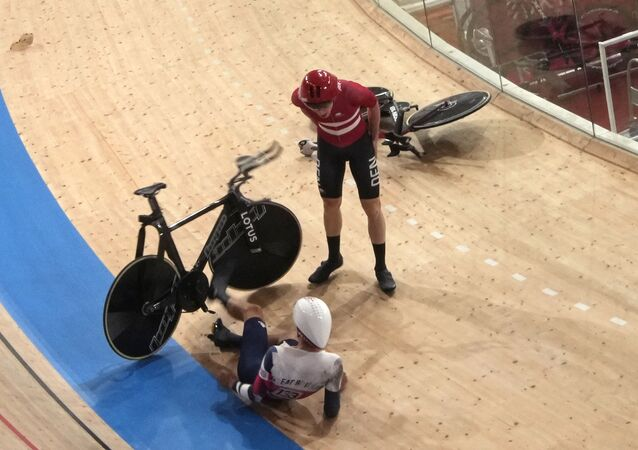 Frederik Madsen of Team Denmark and Charlie Tanfield of Team Britain (133) get up after crashing during the track cycling men's team pursuit at the 2020 Summer Olympics, Tuesday, Aug. 3, 2021, in Izu, Japan.