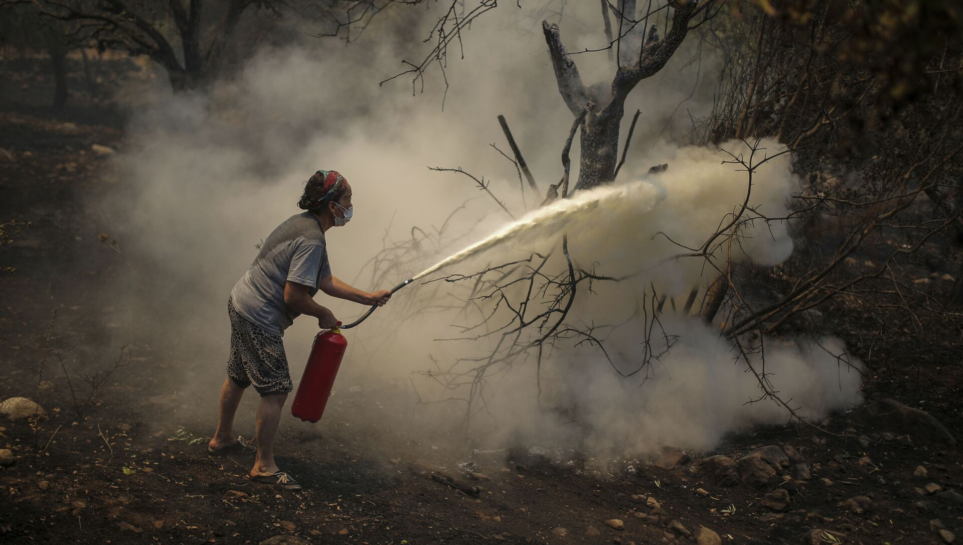 A woman uses a fire extinguisher to save a burning tree in Cokertme village, near Bodrum, Mugla, Turkey, Tuesday, Aug. 3, 2021. - Sputnik International, 1920, 03.08.2021