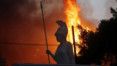 A statue of goddess Athena is seen as wildfire burns at Varympompi suburb north of Athens, Greece, 3 August 2021.