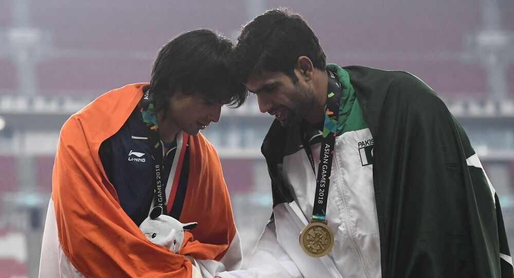 Gold medallist India's Neeraj Chopra (L) shakes hands with bronze medallist Pakistan's Arshad Nadeem during the victory ceremony for the men's javelin throw athletics event during the 2018 Asian Games in Jakarta on August 27, 2018.