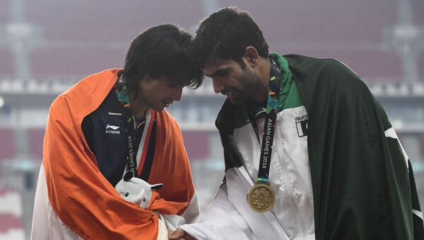 Gold medallist India's Neeraj Chopra (L) shakes hands with bronze medallist Pakistan's Arshad Nadeem during the victory ceremony for the men's javelin throw athletics event during the 2018 Asian Games in Jakarta on August 27, 2018.  - Sputnik International