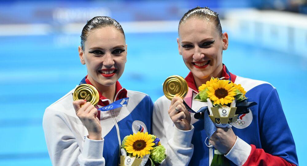 Russian artistic swimming duo, Svetlana Kolesnichenko and Svetlana Romashina (R), react after they won gold for their freestyle routine at the 2020 Tokyo Olympics, 4 August 2021
