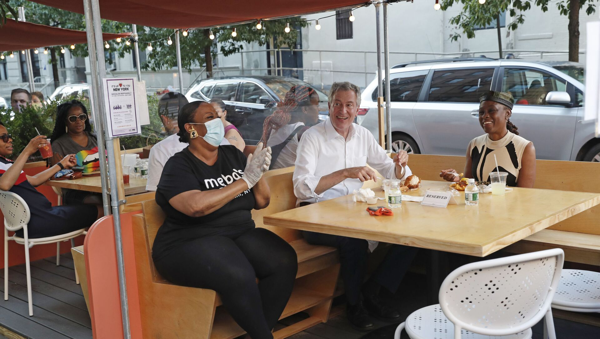 New York Mayor Bill de Blasio, center, laughs as he talks to the parents of a six-year-old child who thanked him for reopening the city's playgrounds as he dined in an outdoor booth with wife Chirlane McCray, right, and restaurant owner Melba Wilson at Melba's in Harlem on the first day of the Phase 2 reopening of the city during the coronavirus pandemic Monday, June 22, 2020, in New York. - Sputnik International, 1920, 04.08.2021