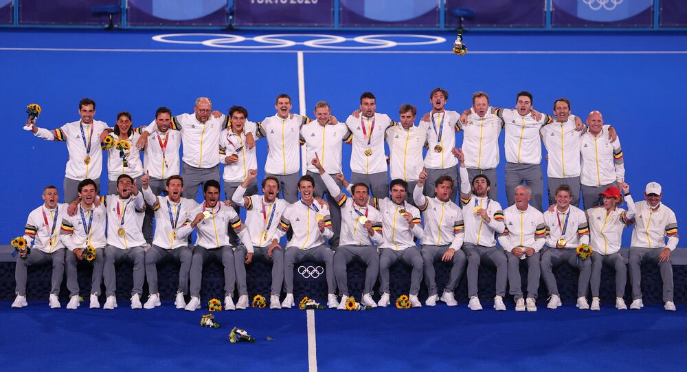 The players and staff of Belgium celebrate as they pose for pictures on the podium after receiving their gold medals.