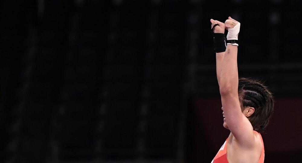 Risako Kawai of Japan celebrates after winning gold against Iryna Kurachkina of Belarus.