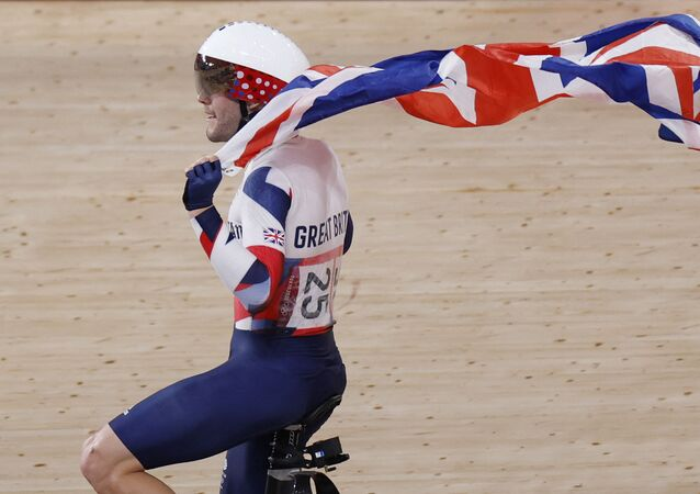 Britain's Matthew Walls celebrates with a flag after winning the men's track cycling omnium points race during the Tokyo 2020 Olympic Games at Izu Velodrome in Izu, Japan, on August 5, 2021.