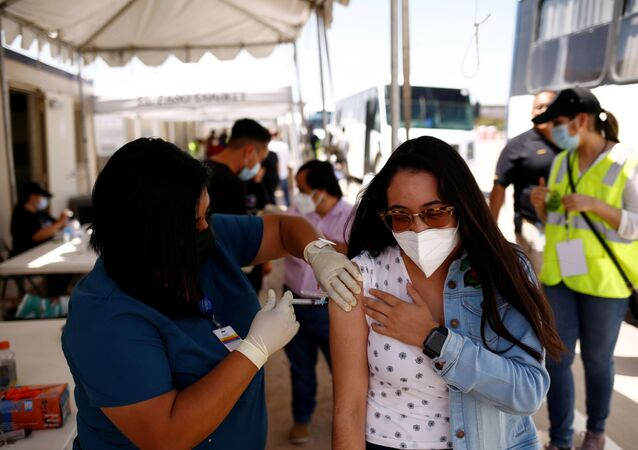 A Mexican woman receives a dose of the Johnson & Johnson coronavirus disease (COVID-19) vaccine, during a binational vaccination program, at the Tornillo-Guadalupe international bridge, in Tornillo, Texas, U.S., July 28, 2021