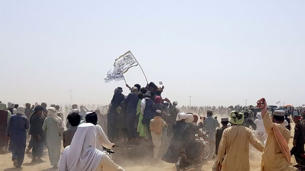 People standing on a vehicle hold Taliban flags as people gather near the Friendship Gate crossing point in the Pakistan-Afghanistan border town of Chaman, Pakistan July 14, 2021. Picture taken July 14, 2021. - Sputnik International