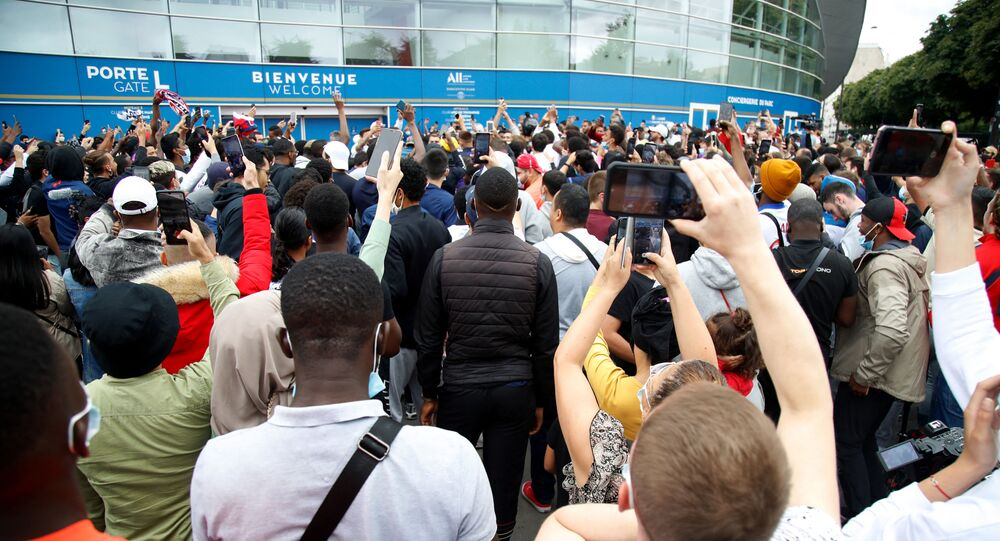 People gather outside the Parc des Princes stadium in Paris as Argentinian football player Lionel Messi is expected to arrive on 9 August 2021, a day after the 34-year-old told at his tearful farewell news conference in Barcelona that joining French football club Paris Saint-Germain was a possibility.