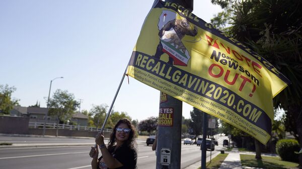 A supporter of the California recall of Gov. Gavin Newsom holds a sign outside of a debate by Republican gubernatorial candidates at the Richard Nixon Presidential Library Wednesday, Aug. 4, 2021, in Yorba Linda, Calif. Newsom faces a Sept. 14 recall election that could remove him from office. - Sputnik International