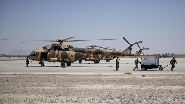 Members of Afghanistan's National Army work near military helicopters, in Kandahar Air Field, Afghanistan, Tuesday, Aug. 18, 2015. Since the departure from Afghanistan last year of most international combat troops, Afghan security forces have been fighting the insurgency alone. Figures show that casualty rates are extremely high, reflecting an emboldened Taliban testing the commitment and strength of the Afghan military. (AP Photo/Massoud Hossaini) - Sputnik International