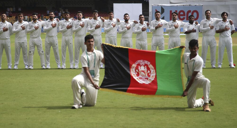Members of Afghanistan cricket team stand for their national anthem before the start of the one-off test match against India in Bangalore, India, Thursday, June 14, 2018