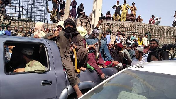 Taliban fighters sit on a vehicle along the street in Jalalabad province on August 15, 2021. - Sputnik International
