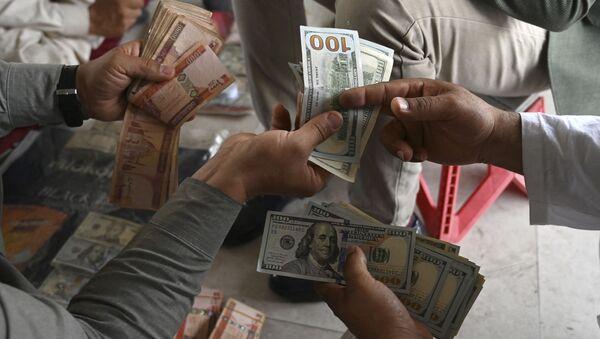 A currency dealer (R) counts US dollars at the Shahzada exchange market in Kabul on 21 June 2021 - Sputnik International