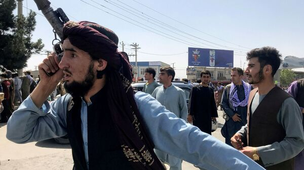 A member of Taliban forces inspects the area outside Hamid Karzai International Airport in Kabul, Afghanistan August 16, 2021 - Sputnik International
