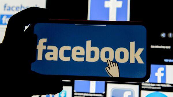 The Facebook logo is displayed on a mobile phone in this picture illustration taken December 2, 2019. - Sputnik International