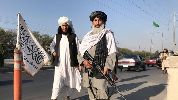 FILE PHOTO: A Taliban fighter holding an M16 assault rifle stands outside the Interior Ministry in Kabul, Afghanistan, August 16, 2021. - Sputnik International