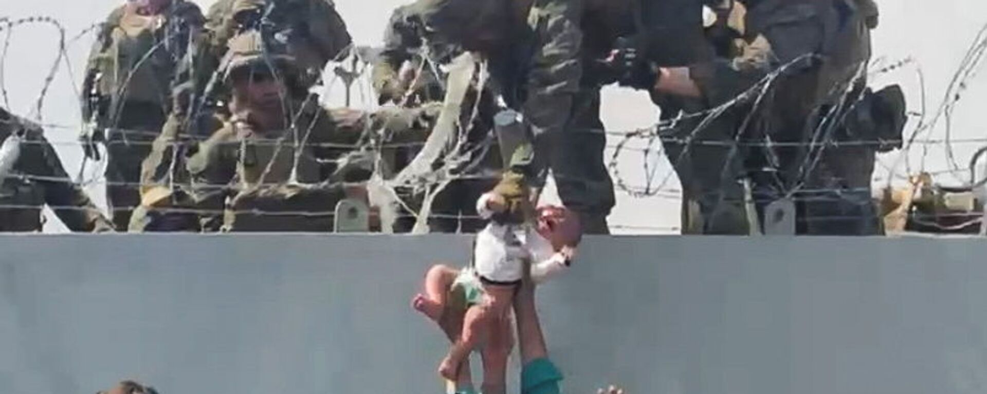 A baby is handed over to the American army over the perimeter wall of the airport for it to be evacuated, in Kabul, Afghanistan, August 19, 2021, in this still image taken from video obtained from social media. - Sputnik International, 1920, 15.09.2021