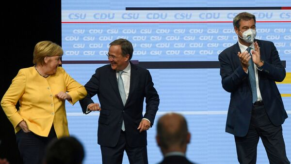 Prime Minister of North Rhine-Westphalia and candidate for chancellor of the CDU/CSU Armin Laschet elbow bumps German Chancellor Angela Merkel as CSU party chief Markus Soeder claps during a CDU/CSU campaign kick off ahead of the federal election at Tempodrom in Berlin, Germany, August 21, 2021. - Sputnik International