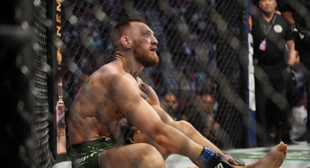 Conor McGregor holds his left ankle while fighting Dustin Poirier during a UFC 264 lightweight mixed martial arts bout Saturday, July 10, 2021, in Las Vegas.