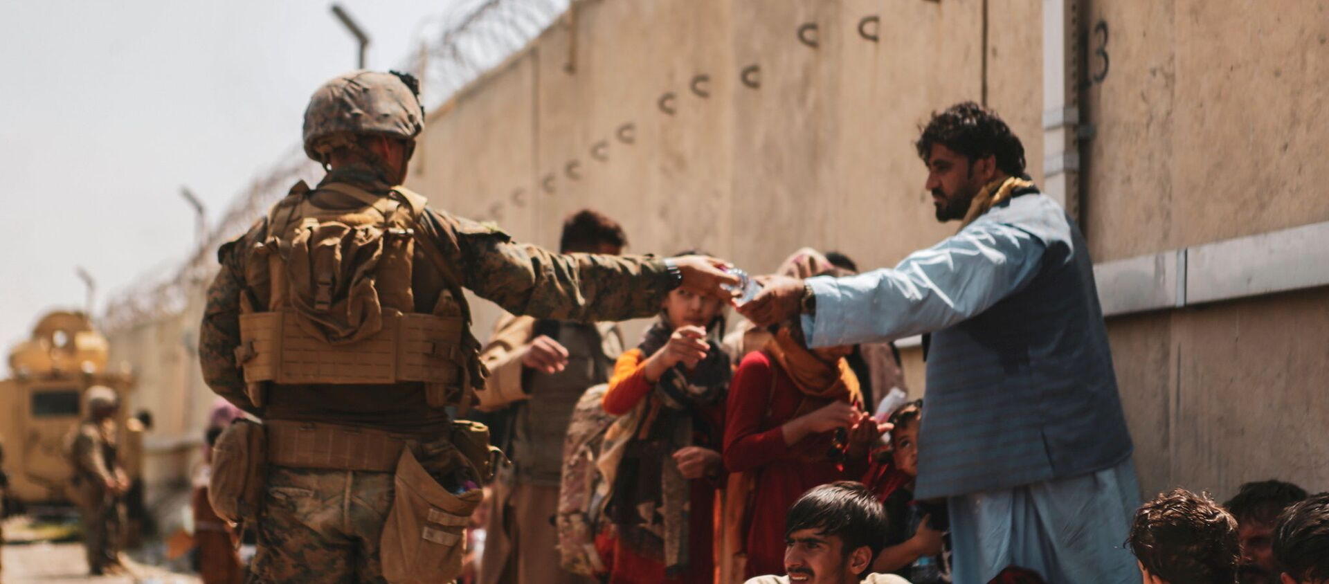 A US Marine passes out water to evacuees during an evacuation at Hamid Karzai International Airport, Kabul, Afghanistan, August 22, 2021 - Sputnik International, 1920, 25.08.2021