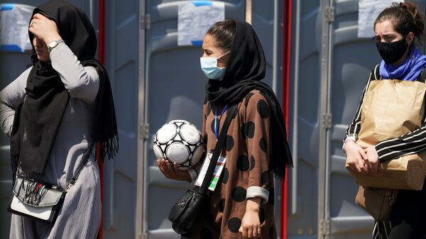 An Afghan woman holding a soccer ball and wearing a CAFA (Central Asian Football Association) credential, waits in line at a processing center for refugees evacuated from Afghanistan at the Dulles Expo Center near Dulles International Airport in Chantilly, Virginia, U.S., August 24, 2021 - Sputnik International