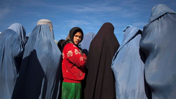 An Afghan girl stands among widows clad in burqas during a cash for work project by humanitarian organisation CARE International in Kabul, Afghanistan January 6, 2010 - Sputnik International
